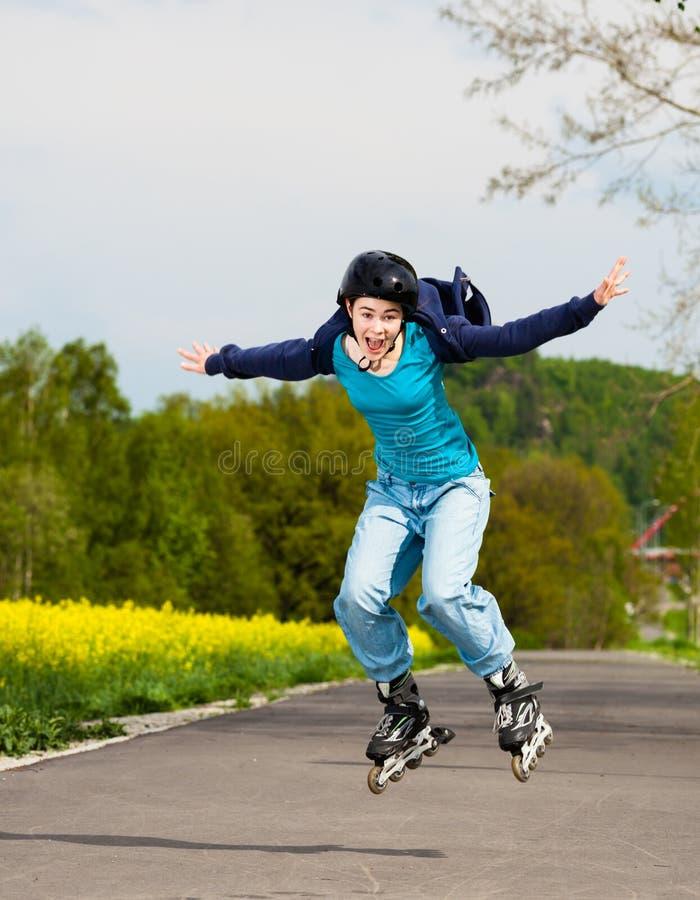 直排轮式溜冰鞋的女孩 免版税库存图片