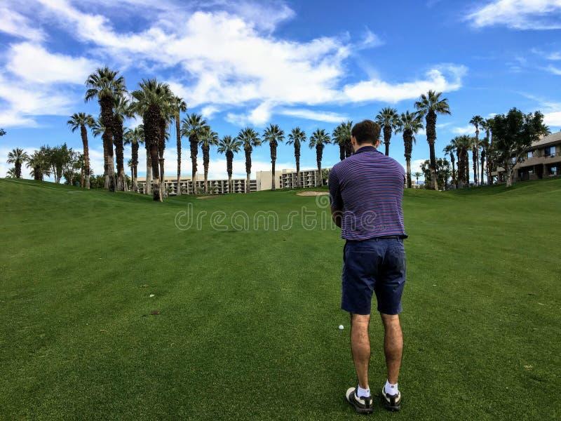 排队他的近射的一位年轻男性高尔夫球运动员从同水准的4航路中在一个高尔夫球场在棕榈泉 免版税库存图片
