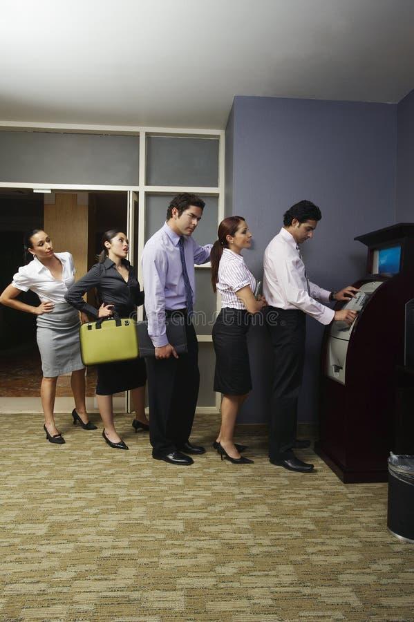 排队在自动售货机的商人 免版税库存照片
