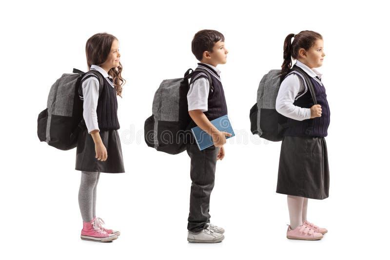 在白色背景排队隔绝的学童全长外形射击图片