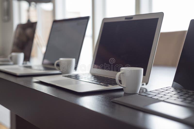 排队的膝上型计算机和浓咖啡 免版税库存图片