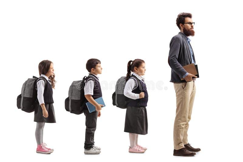 排队behing的男老师的学童 图库摄影