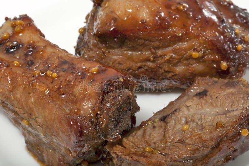 排骨在芥末和蜂蜜调味汁closeu烹调了 免版税库存图片