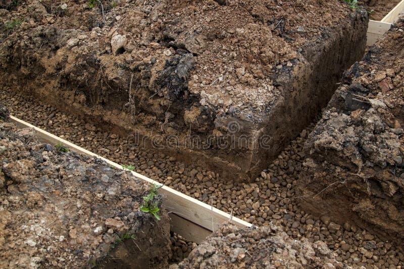 掘沟与瓦砾和模板,为倾吐t准备 库存图片