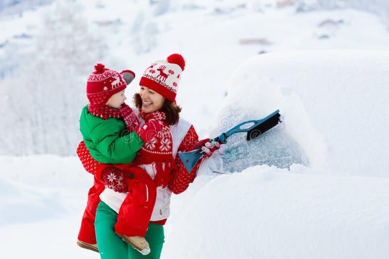 掠过和铲起雪的母亲和孩子汽车在风暴以后 父母和孩子与冬天刷子和刮板清洁家用汽车 图库摄影