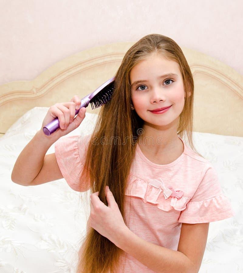 掠过她的头发的逗人喜爱的微笑的女孩孩子画象  免版税库存照片