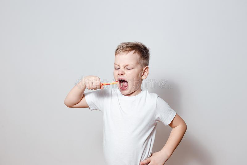 掠过她的牙大开嘴的白色T恤的六岁小孩 库存图片