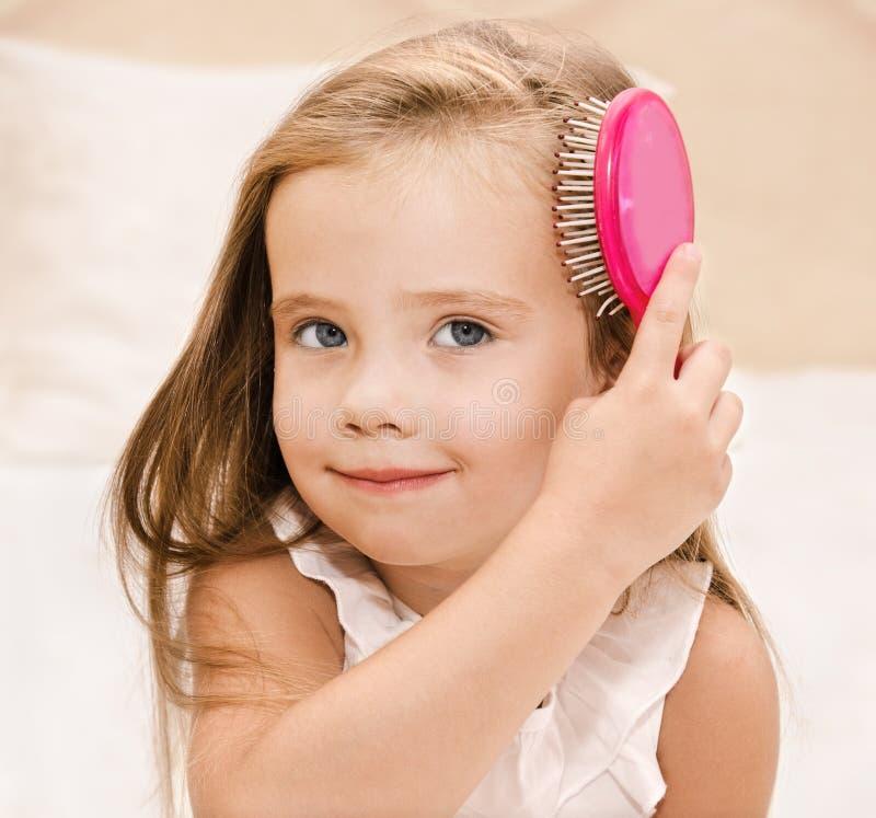 掠过她的头发的微笑的小女孩画象  免版税库存图片