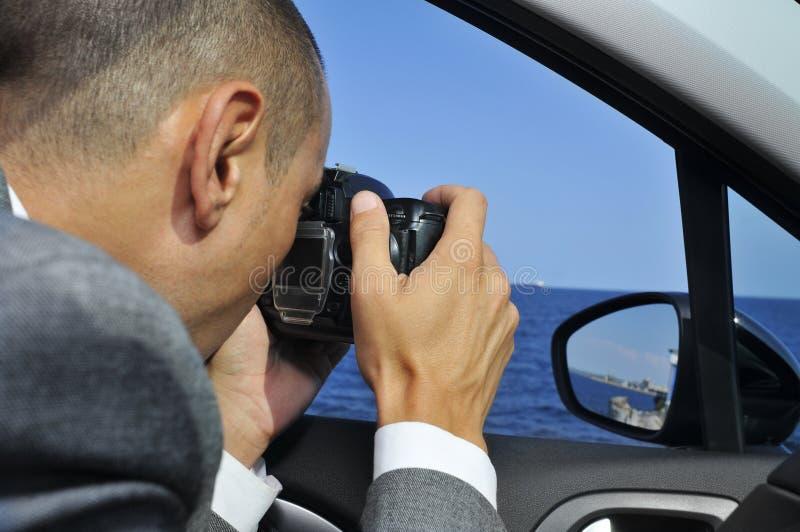 探员或拍照片的无固定职业的摄影师从汽车里边 图库摄影