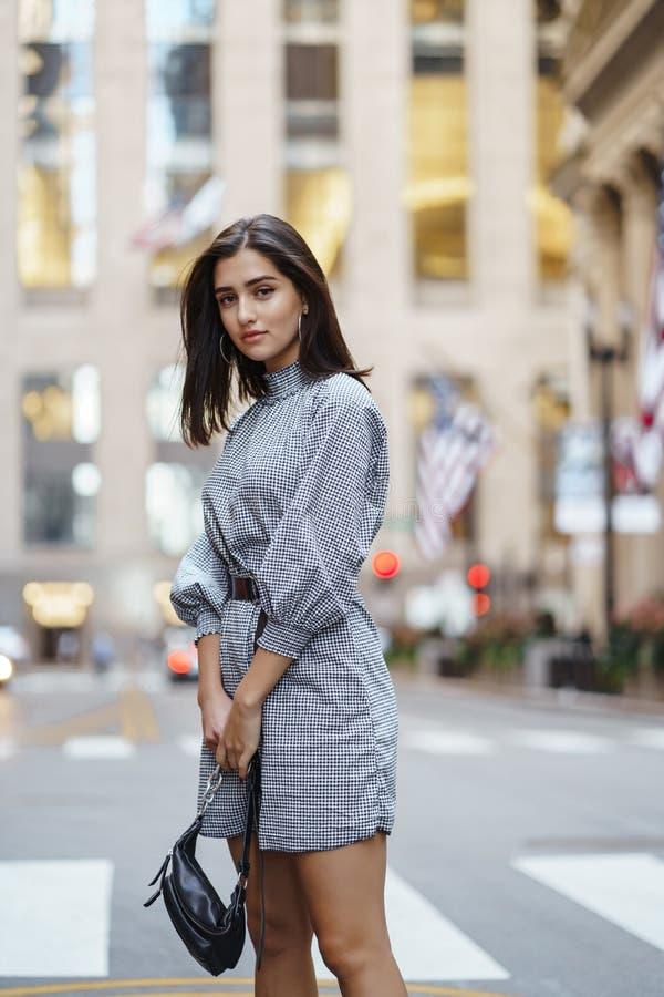 探索城市的美丽的深色的女孩在秋天期间 库存图片