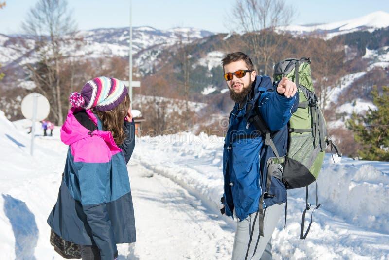 探索多雪的山的远足者夫妇  免版税库存照片