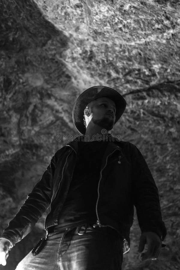 探索巨大的洞的人 冒险旅行家穿戴了牛仔帽和背包,皮夹克 黑白,旅游路线 图库摄影