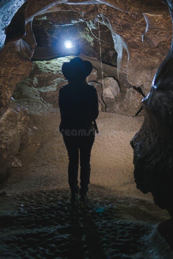 探索巨大的洞的剪影女孩 冒险旅行家穿戴了牛仔帽和背包,皮夹克 垂直的照片,游人 免版税库存照片