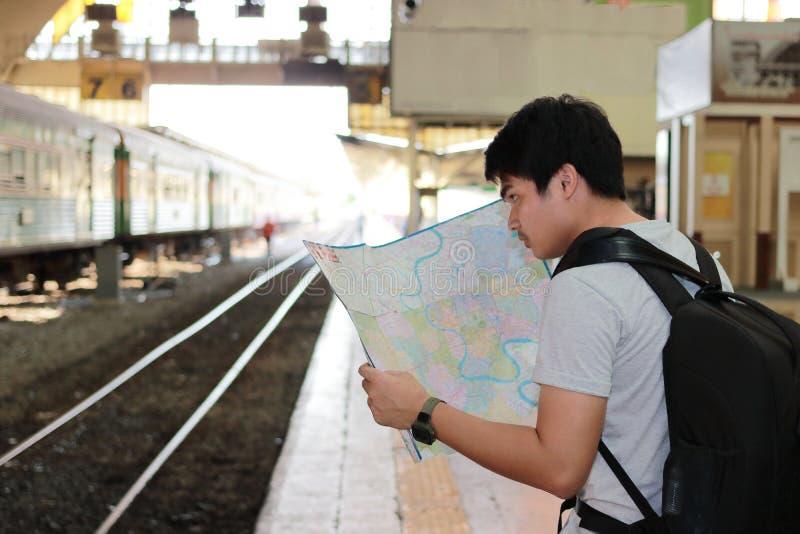 探索正确的方向的英俊的年轻亚裔游人背面图地图在火车站 旅行和旅游业概念 免版税库存照片