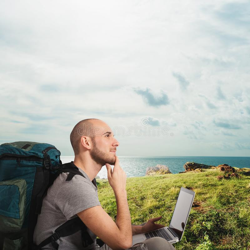探险家计划一次新的旅行对与他的膝上型计算机的一个热带海滩 库存图片