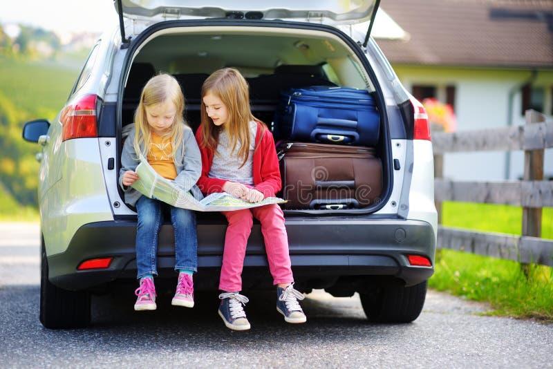 探索地图的两个可爱的妹在继续前与他们的父母的假期 免版税库存照片