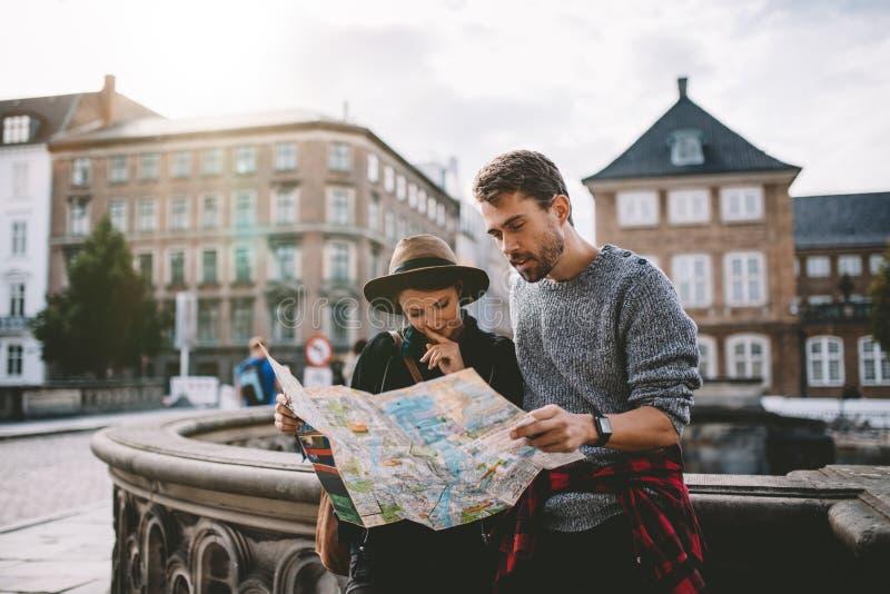 探索城市地图的年轻旅游夫妇 免版税库存图片