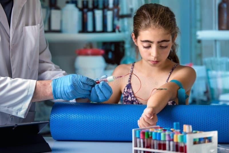 接受一个女孩的血样考试的诊所的医生 库存图片