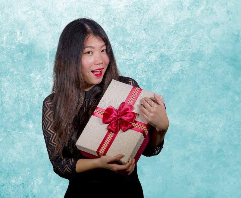 接受一个浪漫周年礼物盒的年轻愉快和激动的美丽的亚裔日本妇女画象对负 免版税库存图片