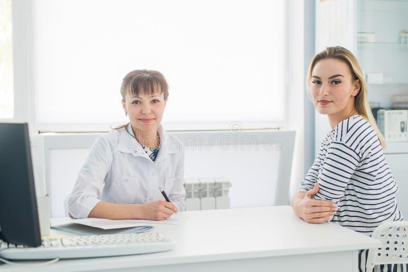接受一次医疗会诊和看照相机的微笑的患者,女性医生在书桌坐 图库摄影