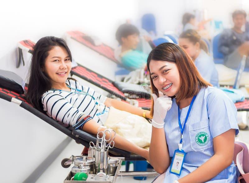 接受与企业女孩的护士献血在医院 免版税库存照片