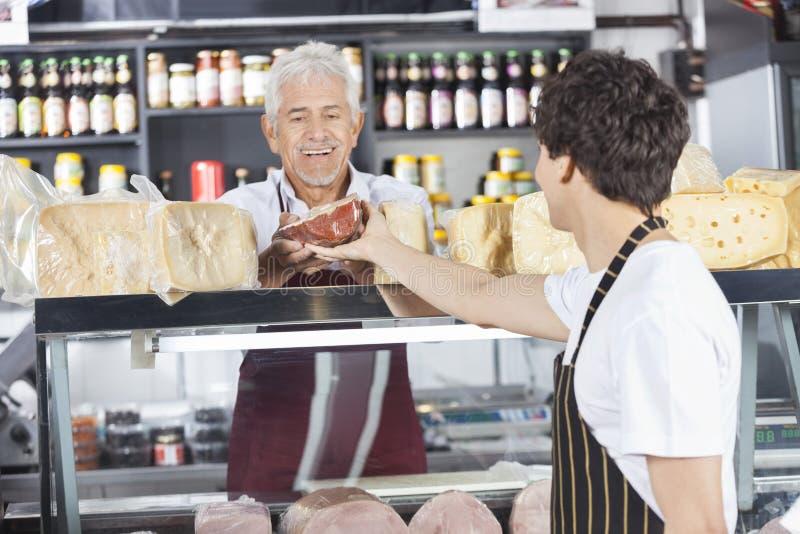 接受乳酪的愉快的推销员从杂货店的同事 免版税库存图片