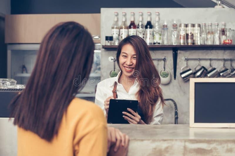 接受从她的客户的亚洲女性咖啡店所有者命令有热烈欢迎微笑的在她的小coffe商店 库存图片
