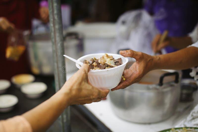 接受从来帮助自由食物断裂志愿者的手的叫化子的手食物:贫穷的社会问题帮助了 库存图片