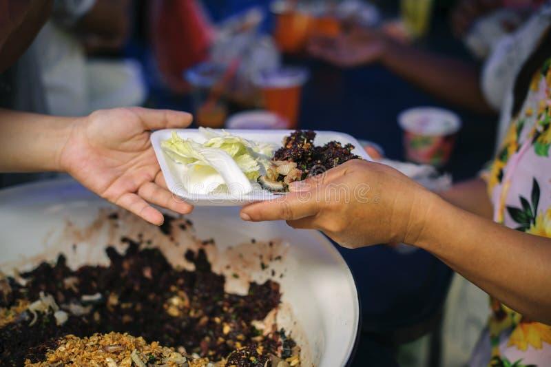 接受从来帮助自由食物断裂志愿者的手的叫化子的手食物:贫穷的社会问题帮助了 免版税图库摄影