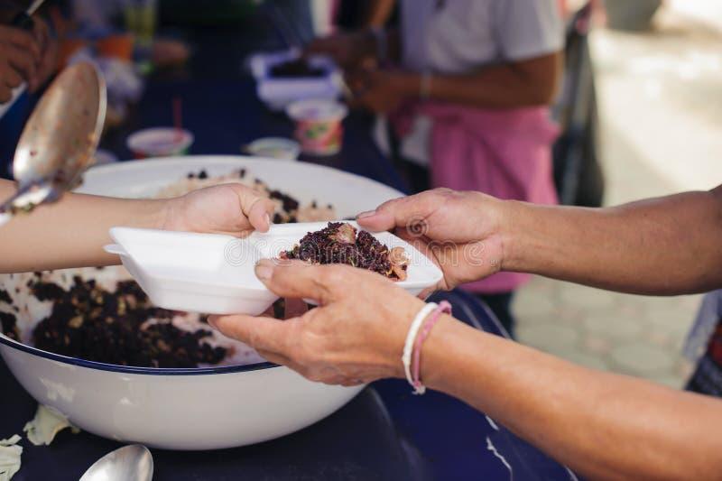 接受从来帮助自由食物断裂志愿者的手的叫化子的手食物:贫穷的社会问题帮助了 库存照片