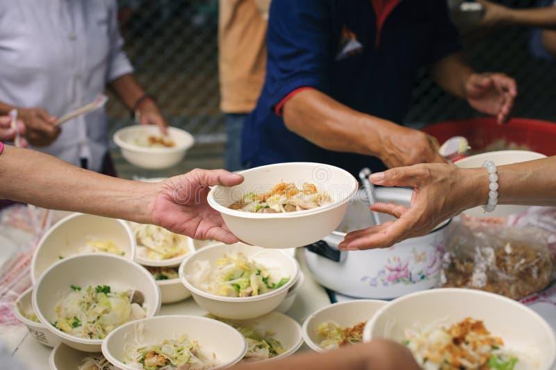 接受从来帮助自由食物断裂志愿者的手的叫化子的手食物:贫穷的社会问题帮助了 免版税库存图片