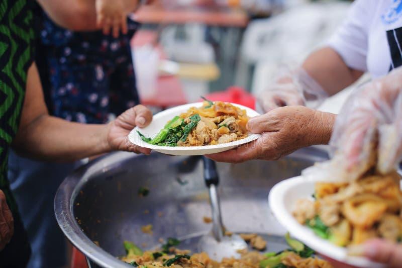 接受从来帮助自由食物断裂志愿者的手的叫化子的手食物:贫穷的社会问题帮助了 免版税库存照片