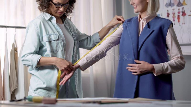 接受企业制服的女装设计师生产命令,个体测量 库存照片
