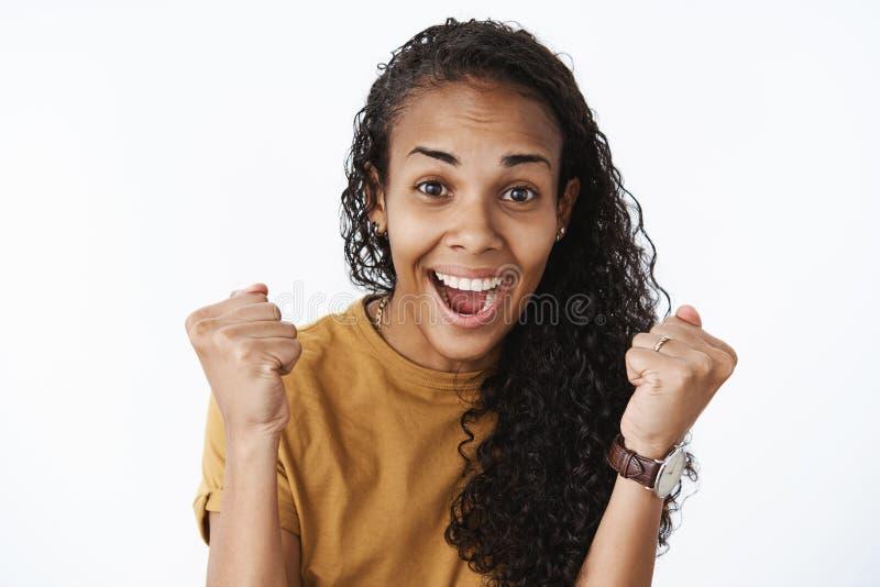 接受促进感觉兴奋的和满意的紧握拳头的高兴愉快的幸运非裔美国人的女孩  图库摄影
