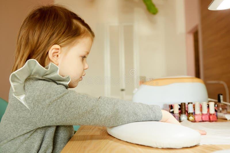 接受修指甲的钉子沙龙的小女孩由美容师 可及修指甲的小女孩美容院 免版税库存图片