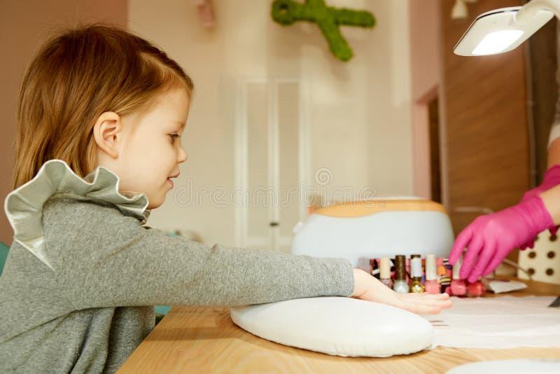 接受修指甲的钉子沙龙的小女孩由美容师 可及修指甲的小女孩美容院 库存照片
