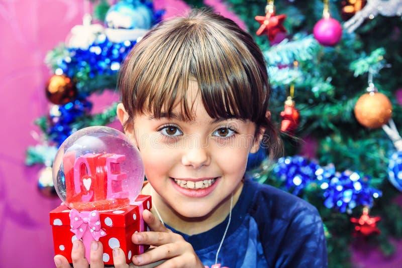 接受充满爱的小女孩雪地球对圣诞节repres 图库摄影