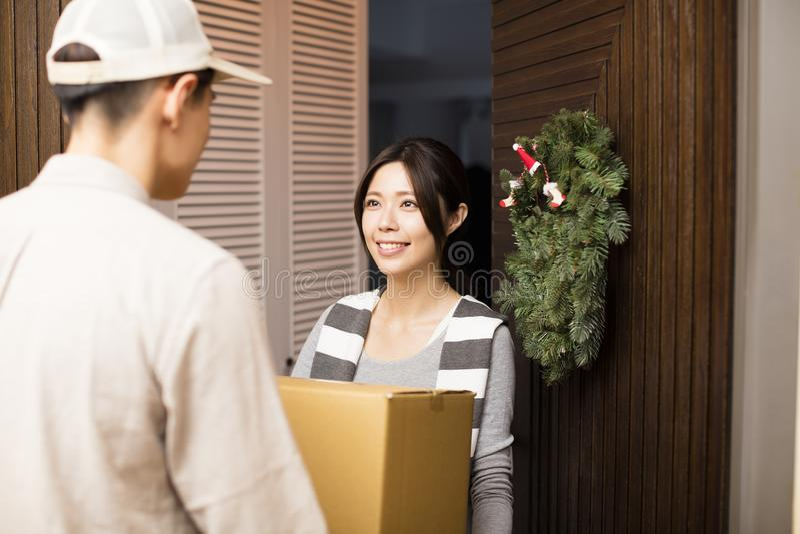 接受包裹的妇女从送货人 免版税库存图片