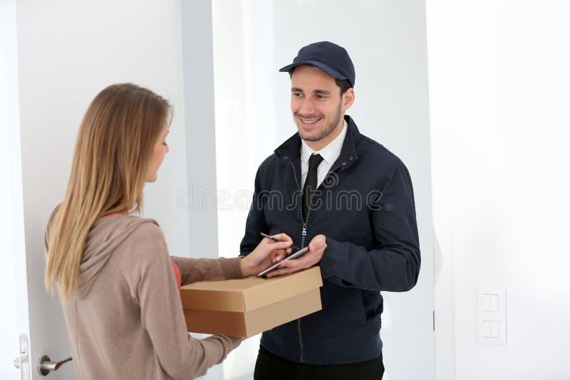 接受包裹的妇女从送货人 库存图片