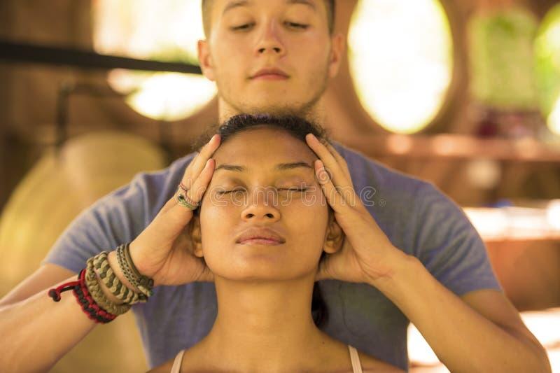 接受医治用的脸面护理和顶头泰国按摩的年轻美丽和轻松的亚裔巴厘语妇女自然生活方式画象  库存照片