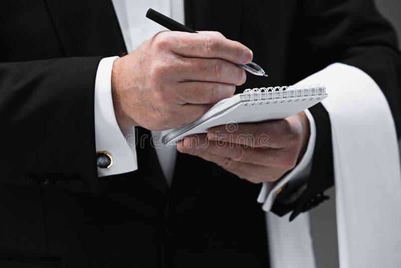 接受命令的侍者穿一件背心在一家花梢餐馆 图库摄影