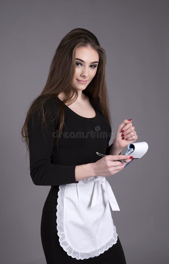 黑接受命令的礼服和白色围裙的女服务员 免版税库存照片