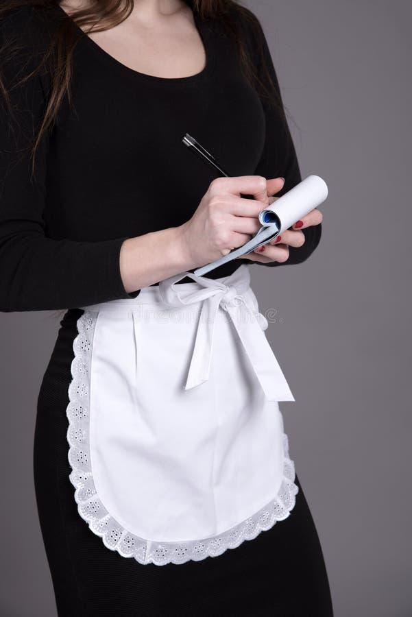 黑接受命令的礼服和白色围裙的女服务员 图库摄影