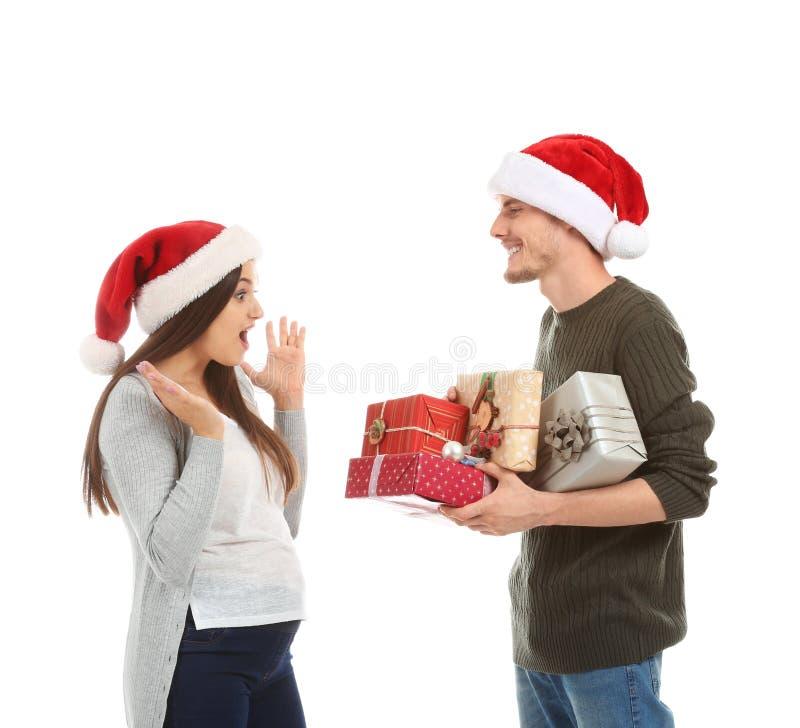 接受圣诞礼物的年轻女人从她的白色背景的丈夫 库存照片