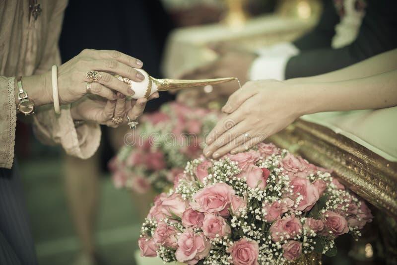 接受圣水的新娘和新郎的手 库存图片