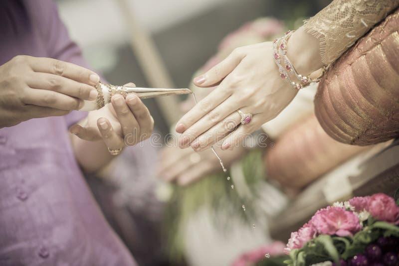 接受圣水的新娘和新郎的手 库存照片