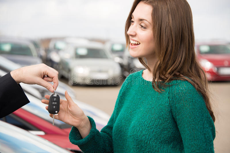 接受在汽车前面的少妇钥匙 免版税库存照片