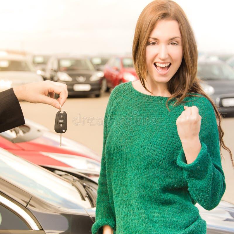 接受在汽车前面的激动的妇女钥匙 免版税库存图片