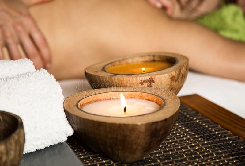 接受在温泉沙龙的少妇后面按摩 一个蜡烛和毛巾的特写镜头 免版税库存照片