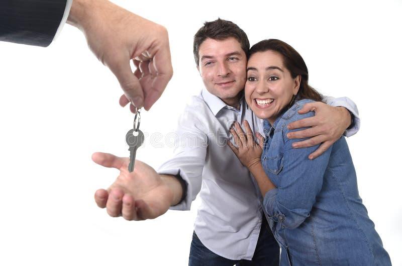 接受在真实状态概念的年轻愉快的夫妇房子关键新的住所 库存照片
